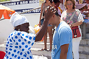 Man being blessed by a Bahiana outside the church. Often the lines between Candomble and Catholicism are blurred. This is especially true with the Sao Lazaro event in late January in Salvador, Bahia, Brazil, the city which is known as the home of Candomble. Sao Lazaro represents healing and the sick.