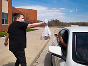 22 APRIL 2020 - DES MOINES, IOWA: SHAWN CLARK hands grab and go lunches to people in a car at Edmunds Elementary School. Schools in Iowa are closed for the rest of the school year because of the COVID-19 (Coronavirus/SAR-CoV-2) pandemic. Des Moines Public Schools expanded their school lunch and distance learning efforts this week. Lunches are being distributed at all of the district's elementary and middle schools and officials have started distributing computers so students can participate in distance learning. The meal distribution was done according to social distancing guidelines.           PHOTO BY JACK KURTZ