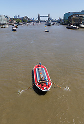 © Licensed to London News Pictures. 30/06/2018. London, UK.  Competitors take part in the 43rd annual Thames Barge Driving Race as they pass Tower Bridge. Crews drive, 30 ton barges that are up to 100 years old using 15 feet long oars along a 7 mile course, starting in Greenwich and finishing in Westminster. The event commemorates the skills of traditional Thames Waermen and Lightermen who used to move freight around on the Thames by barge, under the power of oars. Photo credit: Vickie Flores/LNP