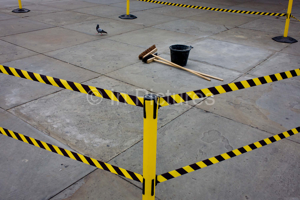 Brushes and bucket on the ground, surrounded by hazard tape in Trafalgar Square, central London. In a scene that might suggest a strike or redundancy, we see the downed tools of a workman who has stopped doing his job or halted for a moment. The two brushes and the black bucket are left in the middle of the tape cordon, stopping visitors to this location from walking through the works site.