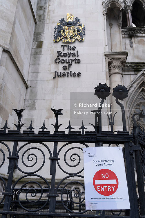 A No Entry sign has been placed on the railings outside the Royal Courts of Justice (The High Court) outside the Royal Courts of Justice, during the third lockdown of the Coronavirus pandemic, on 3rd February 2021, in London, England. Judicial and legal proceedings have been put under great pressure during continued lockdowns with hearings and court cases severely delayed.