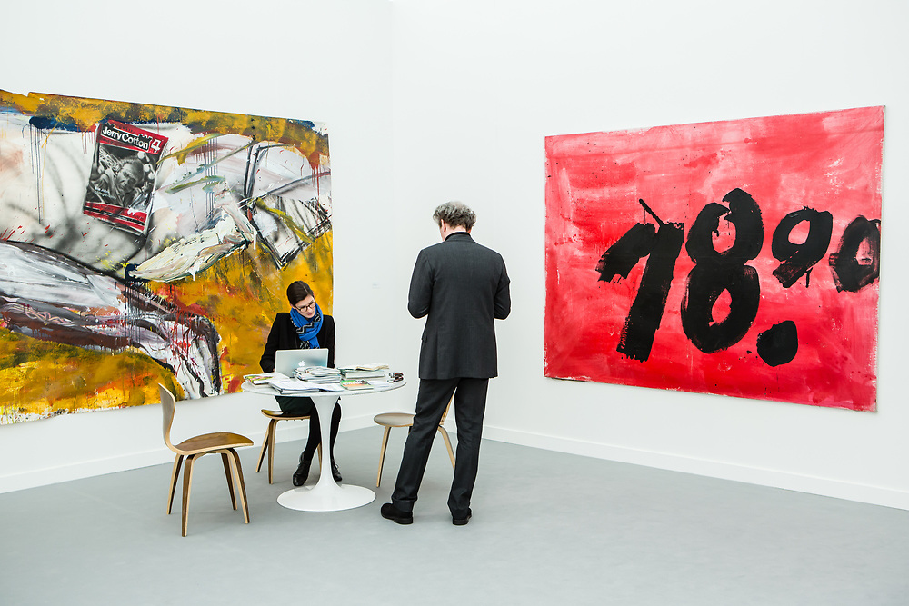 New York, NY - 5 May 2017. The opening day of the Frieze Art Fair, showcasing modern and contemporary art presented by galleries from around the world, on Randall's Island in New York City. Gallerists from Galerie Klaus Gerrit Friese with two untitled paintings by Dieter Krieg.