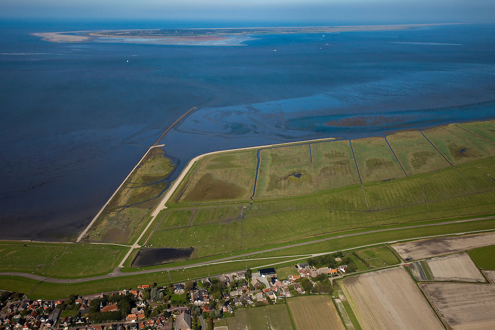 Nederland, Friesland, Gemeente Dongeradeel, 08-09-2009; Paesens-Moddergat met Peazemerlannen, kweldergebied grenzend aan het Wierumerwad en de Waddenzeee. Het gebied is ontstaan door spontane uitpoldering bij storm in 1973 waarbij er een gat geslagen werd in de bitumendijk. Het natuurgebied is in beheer bij  It Fryske Gea. Aan de horizon de Schiermonnikoog..The village Paesens and Peazemerlannen, salt marshes bordering the Wierumerwad and Waddenzeee. The area has been created in 1973, a severe storm made a hole in the outside polder dike. Below the seawall (delta height),  in the middle the dike  of the summer polder. The area is a nature reserve, managed by It Fryske Gea.luchtfoto (toeslag); aerial photo (additional fee required); .foto Siebe Swart / photo Siebe Swart