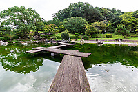 """Josei Park, Kochi Castle Garden - Although Kochi Castle has no existing Japanese garden in its modern incarnation, Josei Park just outside of the castle grounds provides a pleasant introduction to a visit to Kochi-jo.  The pond garden is modern in design with a wooden zig-zag bridge over the pond with a stone garden at its edge.  The arrangement of stones is one of the most important elements in a Japanese Garden.  In the oldest preserved manual of Japanese gardening, garden making was called """"placement of stones"""".   Zen gardens with their stone arrangements are usually the first association people have when considering Japanese gardens whether they are associated with Zen Buddhist, or not."""