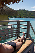 Woman sunbathing on deck of overwater bungalow, Bora Bora, French Polynesia
