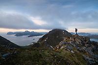 Female hiker overlooks moutain landscape from Middagstind, Flakstadøy, Lofoten Islands, Norway