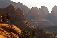 A young man rides his mountain bike on slickrock near Sedona, Arizona.