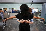 Female security operative feels around a lady passenger's back for suspect items during search at Heathrow Airport's T5