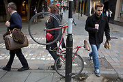Bicycle chained to a lamppost at an awkward angle and at an inconvenient place beside a road crossing in Covent Garden, London, UK.