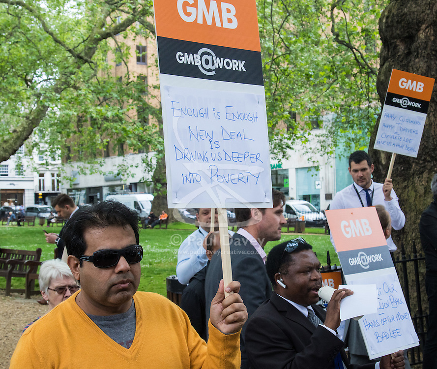 """Mayfair, London, May 24th 2016. Drivers from minicab operator Addison Lee bring traffic to a standstill in Berkely Square, outside of the offices of owner Carlyle Group, in protest against new """"unfair"""" pay rates as the company battles to compete with cut-price Uber, with some drivers claiming they are earning as little as £4.99 per hour. PICTURED: protesters picket outside Landsdowne House where Carlyle Group is headquartered."""