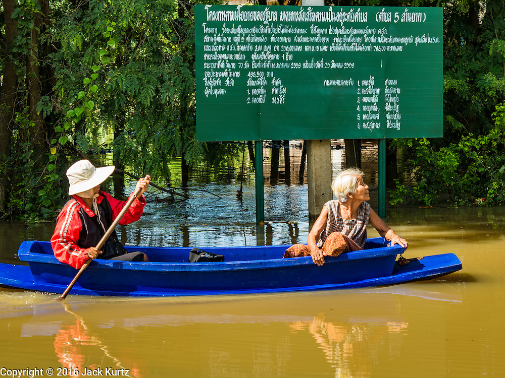 30 SEPTEMBER 2016 - SAI NOI, AYUTTHAYA, THAILAND: Women return to their flooded home in Sai Noi. Many people have stayed in their homes despite the flood waters. They are living in the upper levels of the homes. The Chao Phraya River, the largest river that runs through central Thailand, has hit flood stage in several areas in Ayutthaya and Ang Thong provinces. Villages along the river are flooded and farms are losing their crops due to the flood. This is the same area that was devastated by floods in 2011, but the floods this year are not expected to be as severe. The floods are being fed by water released from upstream dams. The water is being released to make room for heavy rains expected in October.      PHOTO BY JACK KURTZ