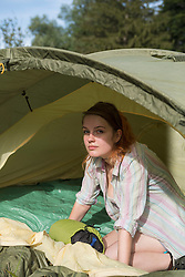 Portrait of a young woman sitting in tent, Bavaria, Germany