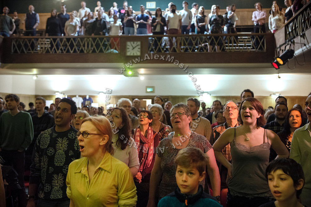 Attendees are singing uplifting lyrics and cheering during The Sunday Assembly (today held inside Conway Hall in central London), an atheist service founded by British comedians Sanderson Jones and Pippa Evans in 2013, in London, England. The gathering is designed to bring together non-religious people who want a similar communal experience to a religious church. Satellite assemblies have been established in over 30 cities including New York, San Diego, and Dublin.