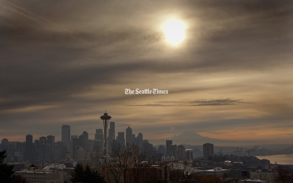 The sun makes a partial appearance amid hazy skies above Seattle and Elliott Bay, with Mount Rainier looming in the background. This view is from Kerry Park on Queen Anne Hill in Seattle. (Ellen M. Banner / The Seattle Times)