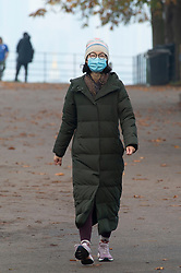 © Licensed to London News Pictures. 06/11/2020.  <br /> Greenwich, UK. A lady wearing a mask going for a walk. People out and about in Greenwich Park, London making the most of their lockdown exercise on a cold November morning. Photo credit:Grant Falvey/LNP