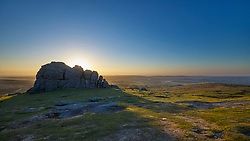 The sun rises behind the impressive granite rocks of Haytor on Dartmoor, Devon England