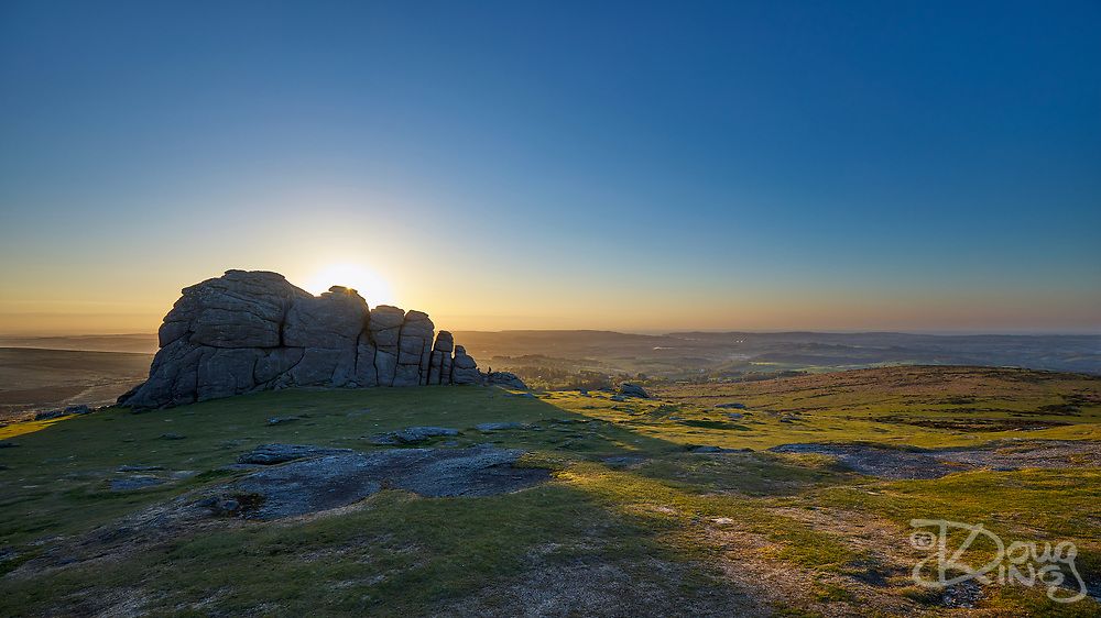 The sun rises behind the impressive granite rocks of Haytor on Dartmoor, Devon England