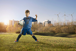 Dirty soccer player cheering on field and wind turbines with city in background, Bavaria, Germany