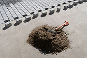 A mound of cement mixture and perfectly-shaped cubed blocks await setting into their places on newly laid-out pavements at Leicester Square, part of the widening of pavements during the third lockdown of the Coronavirus pandemic, on 29th March 2021, in London, England.