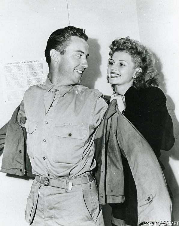 1944 Rita Hayworth helps a soldier put on his jacket at the Hollywood Canteen