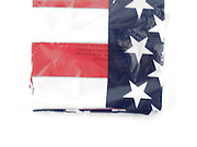 a folded new American flag in plastic wrapper blurry