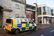 Police officers from Bristol wait outside the prison to carry out a gate arrest. HMP/YOI Portland, a resettlement prison with a capacity for 530 prisoners.