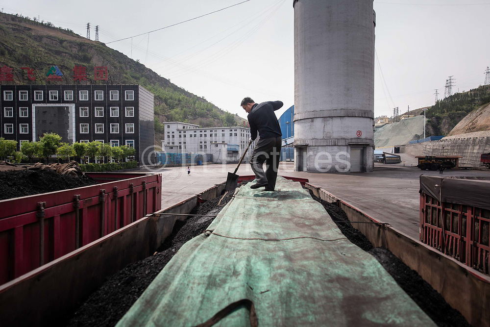 A man shovels coal while standing on the top of a truck at a coal mine and processing facility in Liulin, Shanxi province, China, on Thursday, May 19, 2016. Shanxi is facing a challenge shared by a sweeping region across Chinas industrial north: how to shut down cash-burning mines that employ millions of people whose prospects are uncertain in the new economy promised by President Xi Jinping.