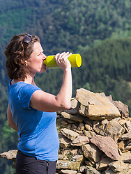 Mature woman drinking water while resting on a hiking tour
