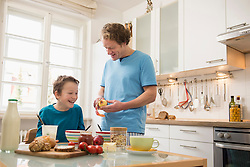 Father peeling apple for son at breakfast table