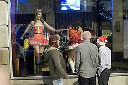 """© licensed to London News Pictures. Manchester, UK 17/12/2011. Ladies in Santa costumes dance in the window of a nightclub as partygoers outside look on. Despite freezing temperatures, """"Mad Friday"""" revellers in Manchester enjoy what is traditionally the busiest night of the year for emergency services, before Christmas. Photo credit: Joel Goodman/LNP"""