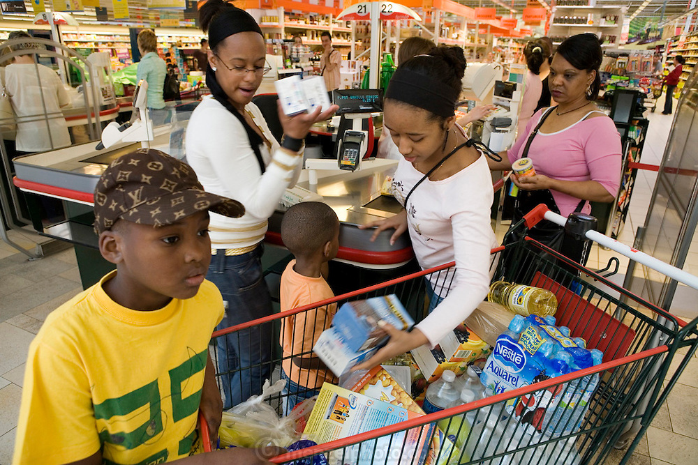 Maria Natercia Lopes-Furtado, and  her  four children: Darlene, Melody, Teddy, and Lionel, from Cabo Verde living in Luxembourg shopping for one week's worth of food at an Auchan super market across the border in France near their home. Grand Duchy of Luxembourg. The image is part of a collection of images and documentation for Hungry Planet 2, a continuation of work done after publication of the book project Hungry Planet: What the World Eats.