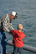Grandfather teaching grandson how to fish from a Valdez pier.