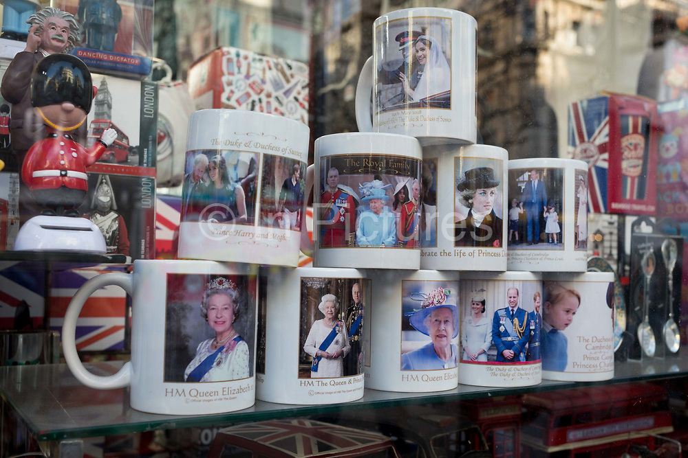 British royal family merchanidise and tourism souvenir mugs which show the faces of Queen Elizabeth, Diana the Princess of Wales and the Duke and the Duke Duchess of Sussex Prince Harry and Meghan Markle on their wedding day, on display in the window of trinket shop in Oxford Street, on 15th January 2020, in London, England.
