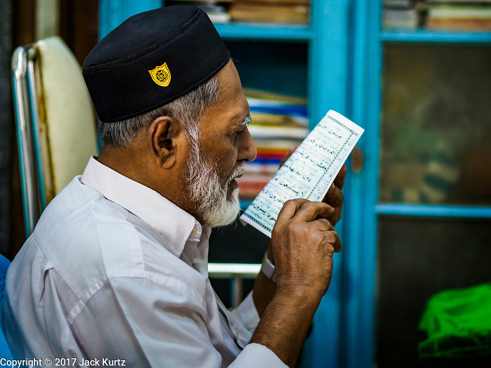 """24 NOVEMBER 2017 - YANGON, MYANMAR: A Muslim man reads a prayer book in Surtee Sunni Jumma Mosque in Yangon. Many Muslims in overwhelmingly Buddhist Myanmar feel their religion is threatened by a series of laws that target non-Buddhists. Under the so called """"Race and Religion Protection Laws,"""" people aren't allowed to convert from Buddhism to another religion without permission from authorities, Buddhist women aren't allowed to marry non-Buddhist men without permission from the community and polygamy is outlawed. Pope Francis is to arrive in Myanmar next week and is expected to address the persecution of the Rohingya, a Muslim ethnic minority in western Myanmar. Some Muslims and Christians are concerned that if the Pope's comments take too strong of pro-Rohingya stance, he could exacerbate religious tensions in the country.  PHOTO BY JACK KURTZ"""