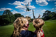A mother and daughter battle the rotor wash as President Donald Trump departs on Marine One from the South Lawn of the White House in Washington, District of Columbia, U.S., on Friday, June 9, 2017. Trump is heading to New Jersey for the weekend.