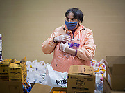 06 APRIL 2020 - DES MOINES, IOWA: LAURIE HICKS, a volunteer, packs food boxes before a drive through emergency food distribution at First DSM Church in Des Moines. On Monday, 06 April, Iowa reported 946 confirmed cases of the Novel Coronavirus (SARS-CoV-2) and COVID-19. There have been 25 deaths attributed to COVID-19 in Iowa. Most non-essential businesses are closed until 30 April. Well over 100,000 Iowans filed first time claims for unemployment in the last three weeks, more than applied during the peak of the Great Recession of 2008. Local food banks have seen an equal spike in people seeking nutritional assistance. First DSM Church has increased their food pantry from one day weekly to three days per week. Hundreds of people lined up Monday to get a box of food and one roll of toilet paper at the church's drive through pantry.         PHOTO BY JACK KURTZ