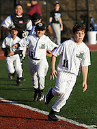 Chester, New York  - Players celebrate by running around the bases after their team won a game in the TRUMP March Madness youth baseball tournament at The Rock Sports Park on March 17, 2012. ©Tom Bushey / The Image Works