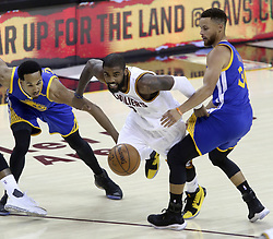 June 7, 2017 - Cleveland, OH, USA - The Cleveland Cavaliers' Kyrie Irving splits the defense of the Golden State Warriors' Shaun Livingston, left, and Stephen Curry in Game 3 of the NBA Finals on Wednesday, June 7, 2017, at Quicken Loans Arena in Cleveland. (Credit Image: © Phil Masturzo/TNS via ZUMA Wire)