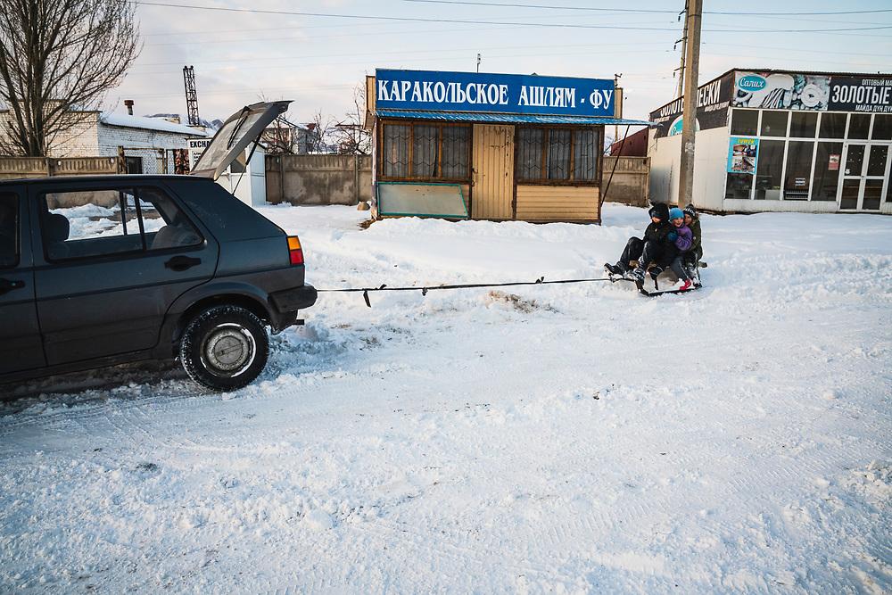 Kids get towed behind a car in Cholpan Ata, Kyrgyzstan.