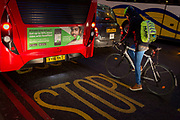 A lady cyclist pauses behind a bus featuring the Farepilot app in winter traffic on Bishopsgate, on 9th February 2017, in the City of London, England. Since January 2009, 84 cyclists over the age of 16 have been killed following crashes with vehicles in Greater London: 33 women and 51 men three children have also died. According to Transport for London, women make only a quarter of our city's bike journeys, yet they represent 39 per cent of adult cycling fatalities in the past six-and-a-half years.