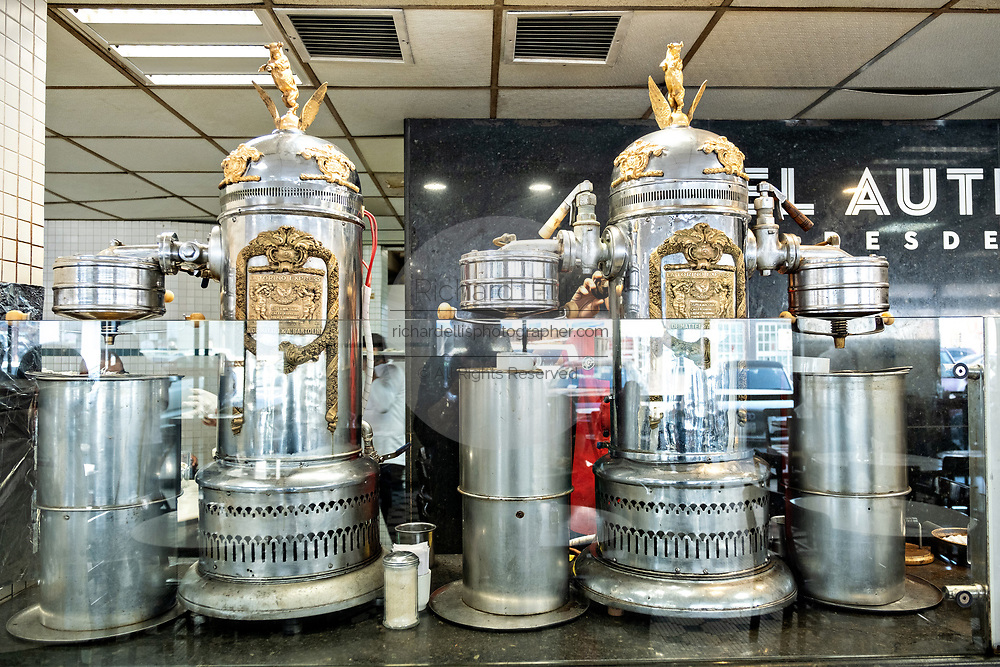 Old style espresso machines at the iconic Gran Café de La Parroquia along the Malecon in Veracruz City, Mexico. The cafe is known for their long pours of hot milky coffee known as a lechero which they have served since 1808 and in their current form has operated continuously since 1926.