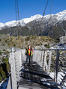 A boy and girl walk across a suspension bridge as they tramp towards the Hooker Valley; Aoraki/Mt. Cook National Park, New Zealand