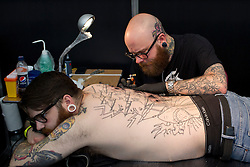 © Licensed to London News Pictures. 25/05/2013. London, UK. A man waits as a tattoo artist inks his back at the Great British Tattoo Show in Alexandra Palace in London today (25/05/2013). The event, which began last year, brings tother world-class tattoo artists artists, vendors and traders and this year takes place on the 25th and 26th of May 2013. Photo credit: Matt Cetti-Roberts/LNP