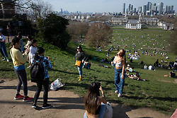 © Licensed to London News Pictures. 30/03/2021. London, UK. Members of the public taker pictures in front of the London skyline in a sunny Greenwich Park in South East London. Temperatures are expected to rise with highs of 23 degrees forecasted for parts of London and South East England today . Photo credit: George Cracknell Wright/LNP