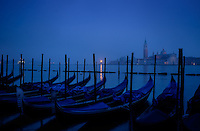 VENICE, ITALY - CIRCA MAY 2015: View of typical Venetian gondolas with the Grand Canal and San Giorgio Maggiore at dawn.