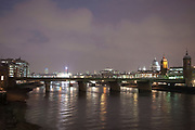 Night scene over the River Thames towards St Paul's Cathedral on a cold winter evening.  The sky glowing from the city lights. Southwark rail bridge crosses at this point as the route in towards Cannon Street station.