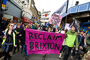 Anti-gentrification protest 'Reclaim Brixton' in central Brixton on 25th April 2015 in the London borough of Lambeth, United Kingdom. Protesters march from Windrush Square along Atlantic Road, passing Brixton Village and Market, in response to recent redevelopment plans which 'are changing the face of Brixton rich and diverse community'.