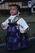 A Japanese toddler walks outside wearing traditional Japanese clothing