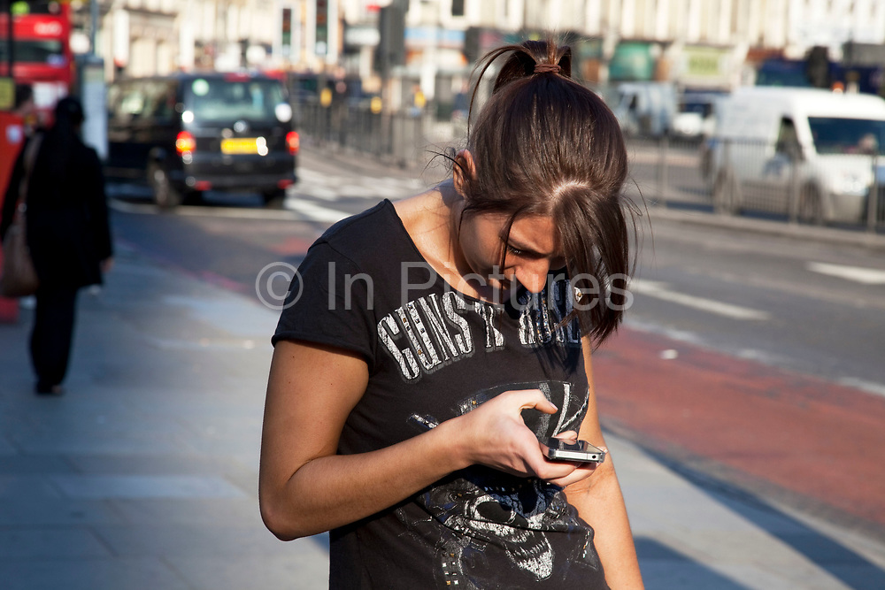 Woman deep in concentration texting on her mobile phone.