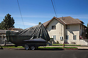 In the North LA suburb near Griffith Park a large sea going boat parked outside a home